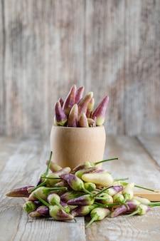 Pimentas com tábua em um vaso na madeira,