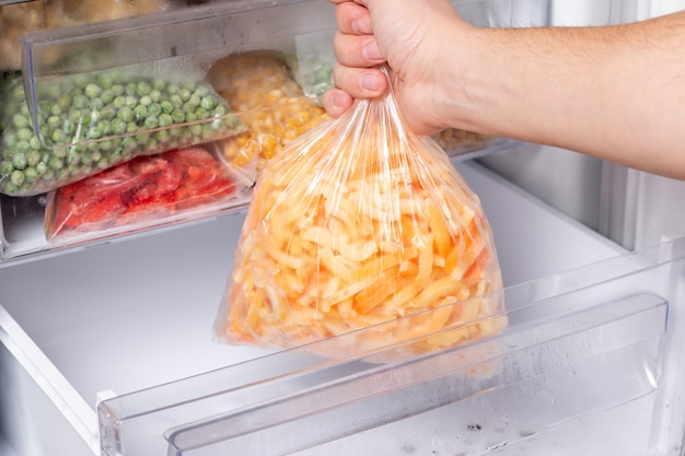 Pimentas congeladas em um saco plástico no congelador. vegetais congelados. conceito de alimentação saudável.