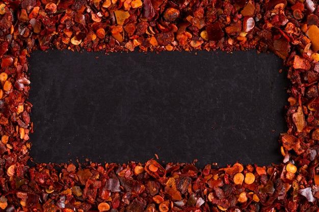 Pimentas de pimentão secadas esmagadas vermelhas, close up na forma de um quadro. copyspace