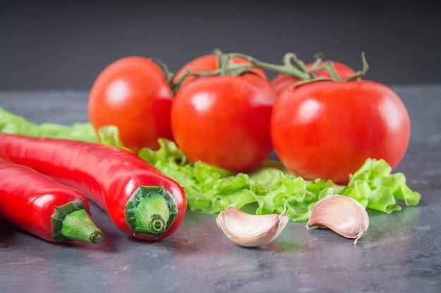 Pimentas de pimentão, tomates, alface, alho em um fundo cinzento.