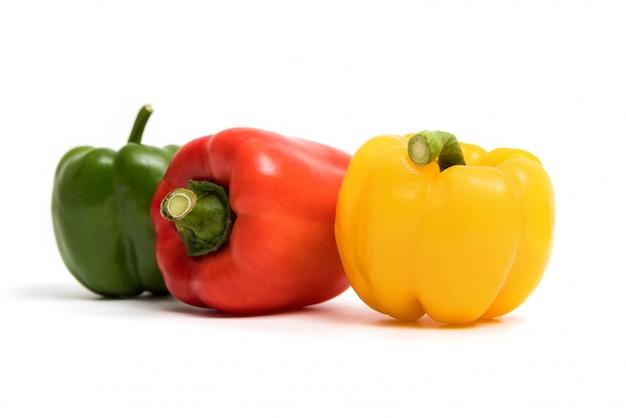 Pimentas de sino doce verdes, vermelhas, amarelas isoladas no fundo branco.