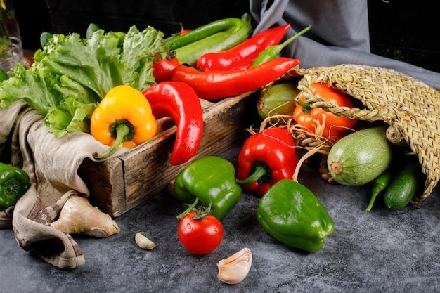 Pimentas e hortaliças na cesta rústica e em uma bandeja de madeira.