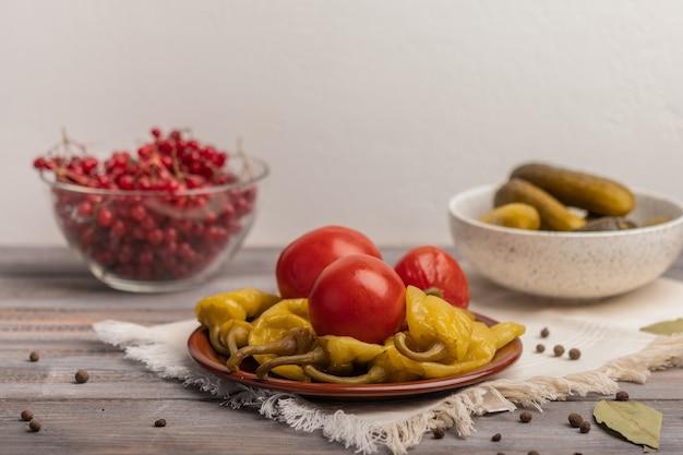 Pimentas e tomates em conserva caseiros em um prato de cerâmica em um guardanapo de linho. perto de picles e viburnum em tigelas. copie o espaço. estilo rústico