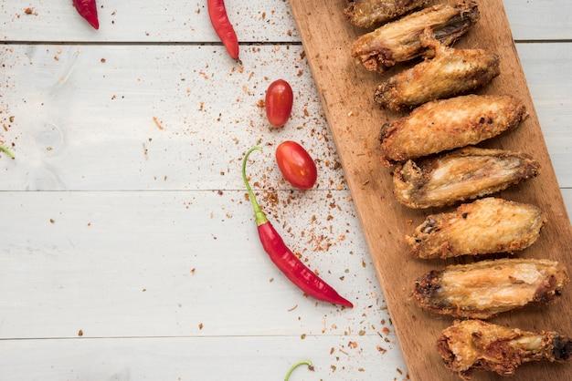 Pimentas e tomates perto de asas de frango