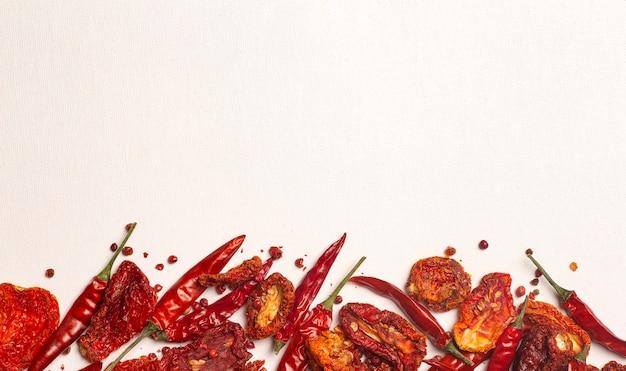 Pimentas e tomates secos ao fundo, pimentões picantes e tomates vermelhos secos ao sol
