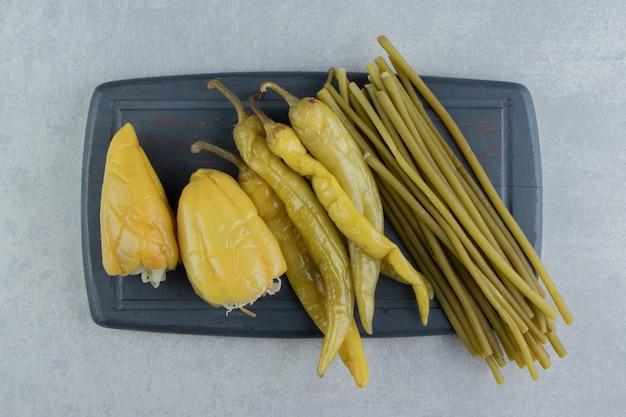 Pimentas e verduras em conserva no quadro escuro.