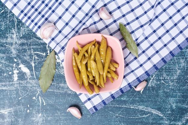 Pimentas em conserva no prato com folha, alho e toalha de mesa.