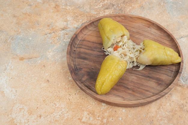 Pimentas em conserva recheadas com chucrute em prato de madeira