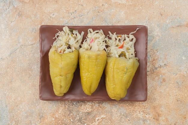 Pimentas em conserva recheadas com chucrute no prato marrom