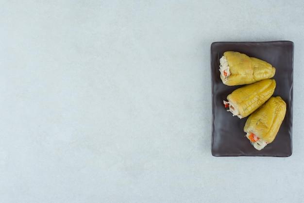 Pimentas em conserva recheadas com legumes na placa preta.