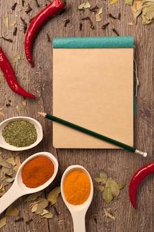 Pimentas, especiarias em colheres, caderno e lápis