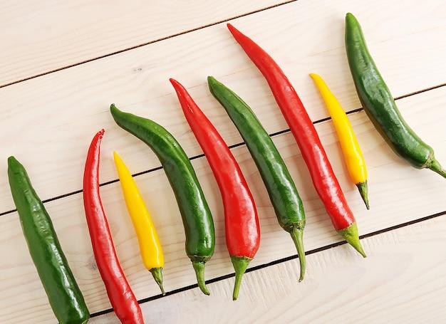 Pimentas estão em uma fileira com pimenta amarela, verde e vermelha