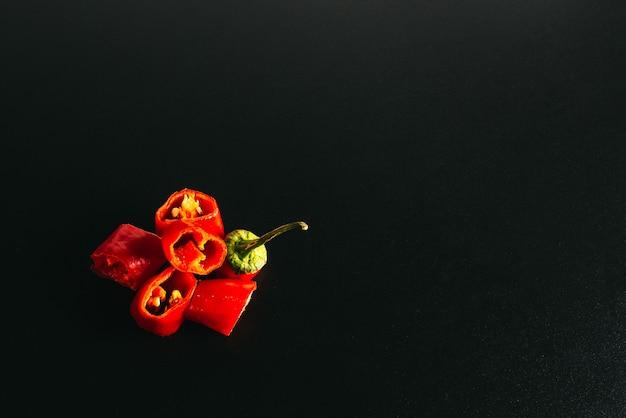 Pimentas frescas, cortadas em pedaços, mentem sobre um fundo preto. copyspace