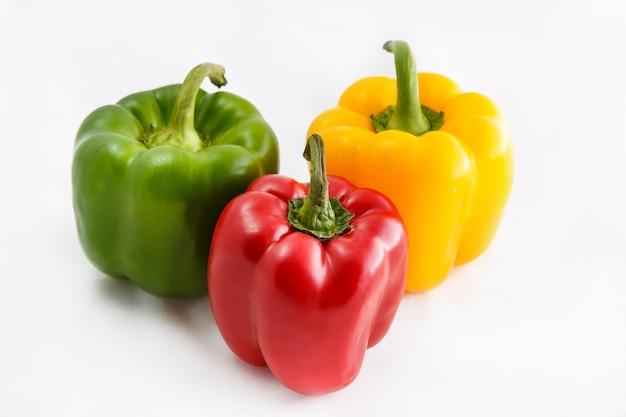 Pimentas frescas. três pimentas vermelhas, amarelas, verdes doces isoladas no fundo branco.