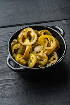 Pimentas jalapeño fatiadas em potes, na mesa de madeira preta