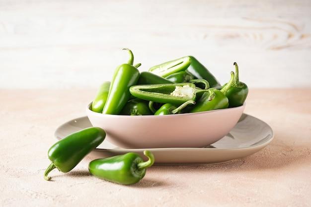 Pimentas jalapeno verdes em um prato sobre um fundo bege.