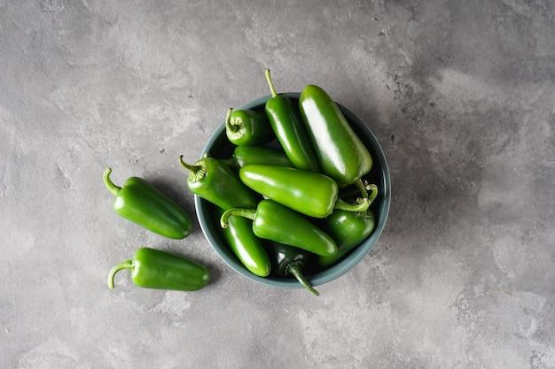 Pimentas jalapeno verdes em um prato sobre um fundo cinza, vista superior.