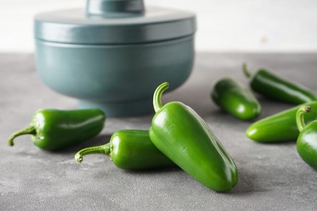 Pimentas jalapeño verdes em uma tigela de cerâmica sobre um fundo cinza. fechar-se.