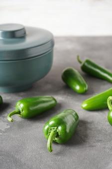 Pimentas jalapeño verdes em uma tigela de cerâmica sobre um fundo cinza. vertical.