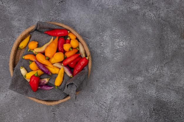 Pimentas peruanas de várias cores na mesa cinza