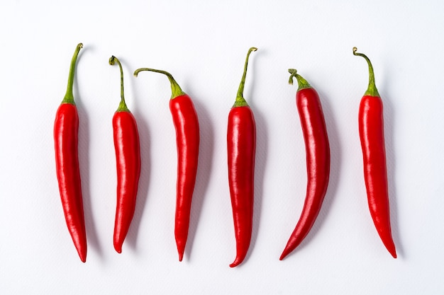 Pimentas picantes do pimentão maduro vermelho sobre o fundo branco.