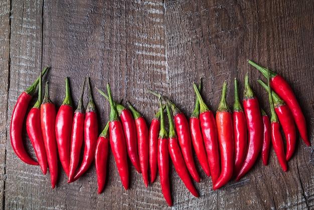 Pimentas quentes do pimentão vermelho na placa de madeira marrom velha.
