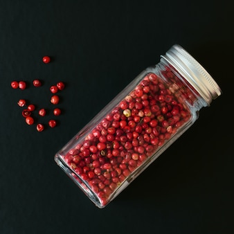 Pimentas rosa em uma jarra transparente em preto