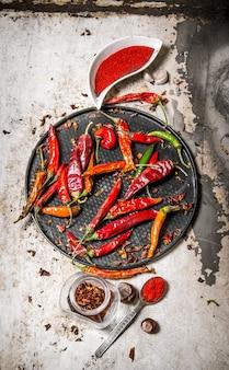 Pimentas secas na bandeja com pimenta vermelha esmagada em xícaras, com ervas na mesa rústica. vista do topo