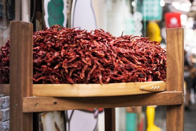 Pimentas secas na cesta de debulha no caso de madeira, foco seletivo