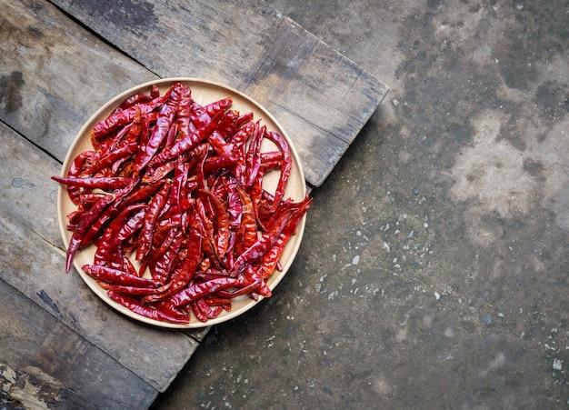Pimentas secas quentes vermelhas em tigela de madeira no chão de madeira, estilo rústico