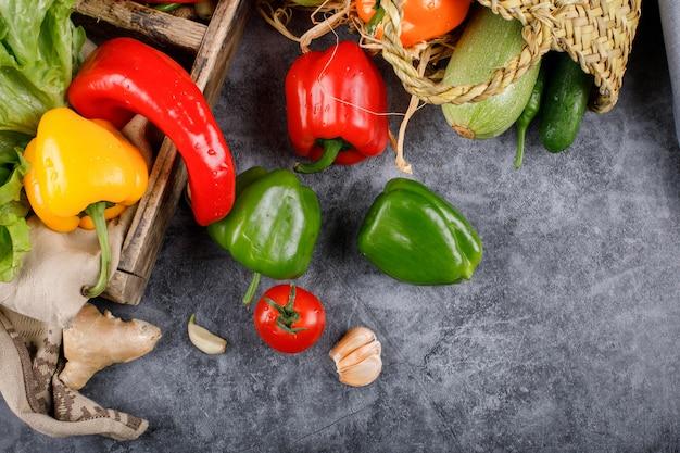 Pimentas, tomate e alho em uma mesa azul.