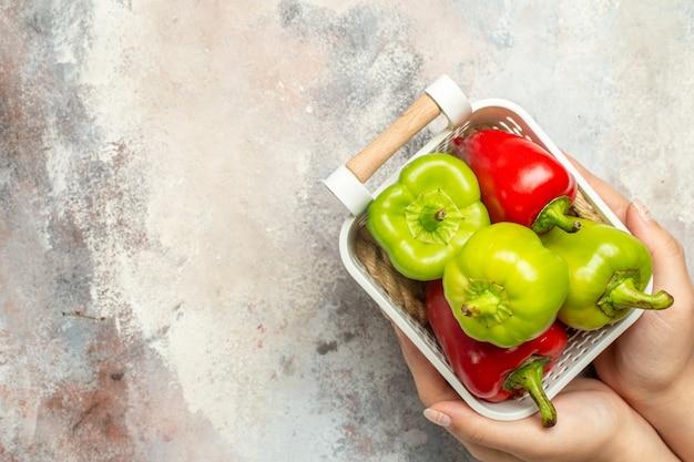Pimentas verdes e vermelhas de cima em uma cesta de plástico na mão feminina na superfície nua com espaço livre