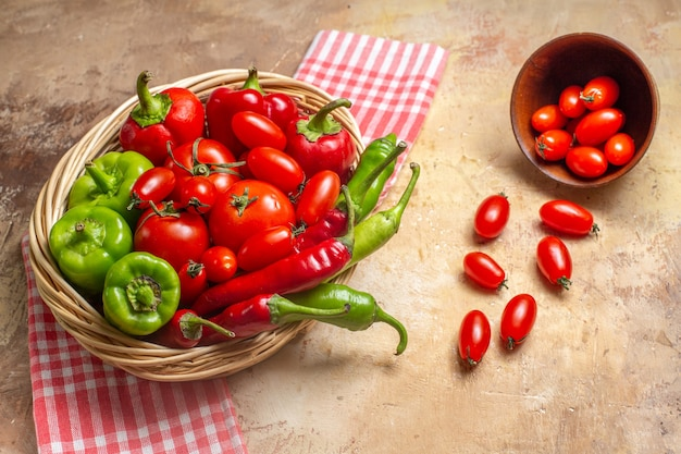 Pimentas verdes e vermelhas, de frente, pimentas, tomates em uma cesta de vime, tomates cereja espalhados da tigela, toalha de cozinha em fundo âmbar