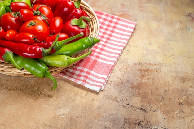 Pimentas verdes e vermelhas, de frente, tomates, pimentas, em cesta de vime, toalha de cozinha em fundo âmbar com espaço livre
