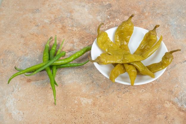Pimentas verdes frescas e em conserva em prato branco