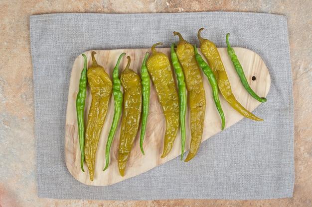 Pimentas verdes frescas e em conserva em uma placa de madeira