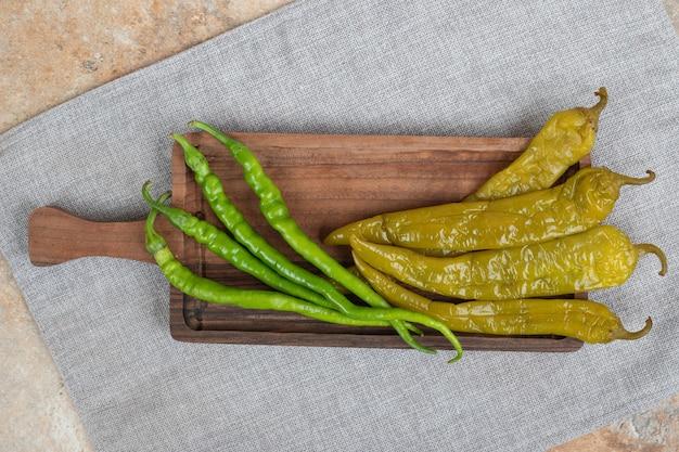 Pimentas verdes frescas e em conserva em uma tábua de madeira