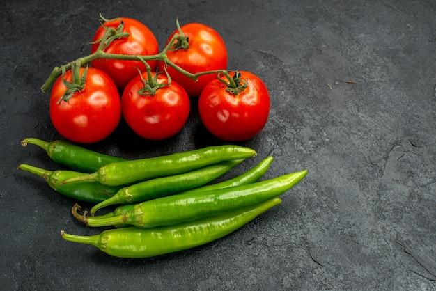 Pimentas verdes picantes de vista frontal com tomates vermelhos