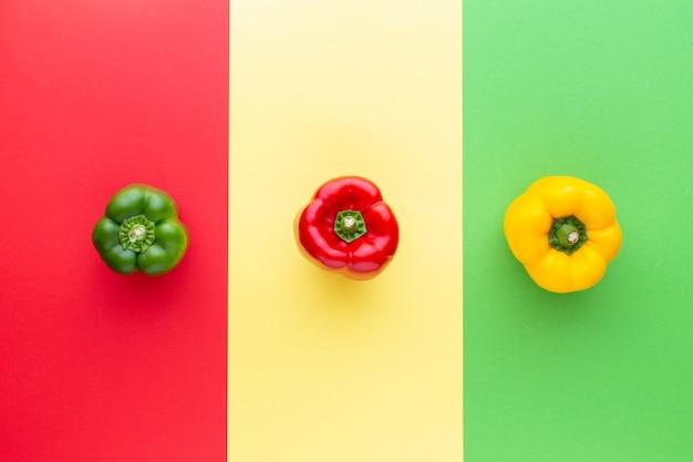 Pimentas vermelhas amarelas e verdes em fundo colorido