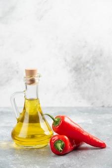 Pimentas vermelhas com uma garrafa de azeite de oliva extra virgem na mesa de mármore.