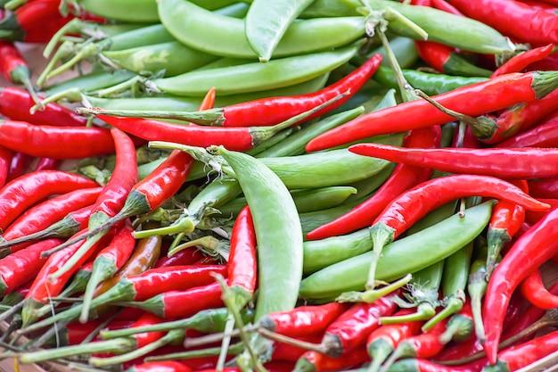 Pimentas vermelhas e ervilhas verdes frescas do jardim.