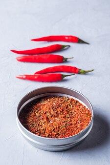 Pimentas vermelhas e flocos de pimenta em fundo cinza
