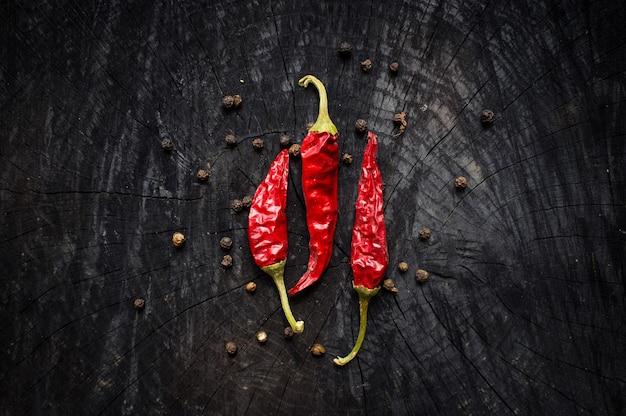 Pimentas vermelhas e grãos de pimenta na mesa de madeira escura