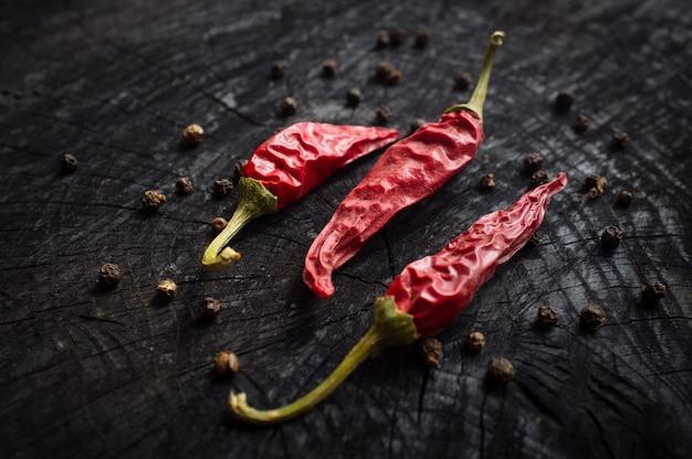 Pimentas vermelhas e pretas em uma mesa de madeira escura