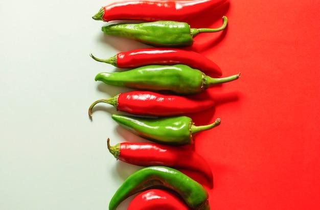 Pimentas vermelhas e verdes em uma superfície branco-vermelha lado a lado. Foto Premium