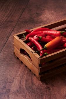 Pimentas vermelhas em uma caixa colocada sobre uma superfície de madeira