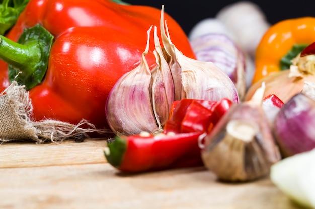 Pimentas vermelhas fatiadas, cebolas, alho inteiro e outros vegetais durante o cozimento