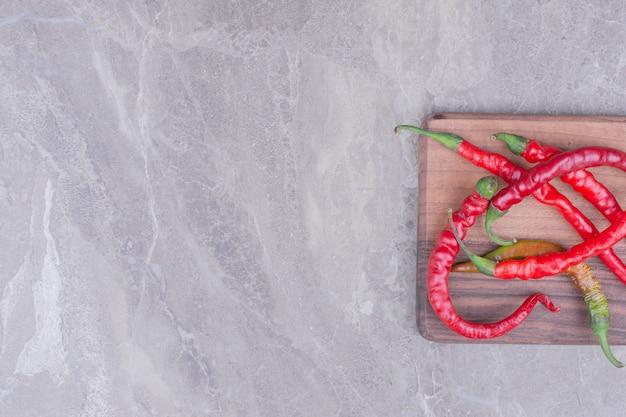 Pimentas vermelhas isoladas em uma placa de madeira na superfície de mármore