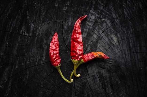 Pimentas vermelhas na mesa de madeira preta
