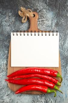 Pimentas vermelhas picantes de vista superior com bloco de notas em comida madura de foto de fundo escuro
